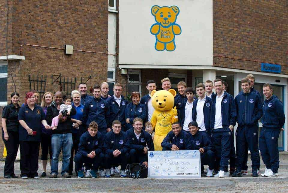 The team pose for a photo with the cheque along with staff